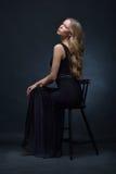 摆在与椅子的一件黑晚礼服的美丽的妇女 免版税库存图片