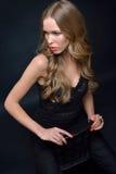 摆在与椅子的一件黑晚礼服的美丽的妇女 免版税库存照片
