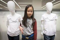 摆在与模型的女孩在时尚商店 免版税库存照片