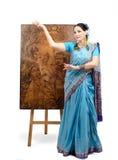 摆在与烙画绘画莲花的印地安莎丽服的艺术家 免版税库存照片