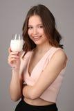 摆在与牛奶酒杯的夫人  关闭 灰色背景 免版税库存图片