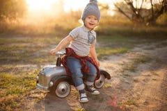 摆在与玩具汽车的小孩 免版税库存照片
