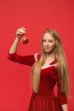 摆在与玩具的红色背景的圣诞老人女孩 免版税图库摄影