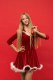 摆在与玩具的红色背景的圣诞老人女孩 免版税库存照片
