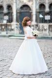 摆在与玫瑰色花束,在背景的都市风景的年轻微笑的新娘 免版税库存图片