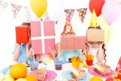 摆在与生日礼物的小孩 免版税库存图片