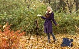 摆在与画架的少女艺术家在秋天公园 免版税库存照片