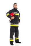 摆在与盔甲的消防队员在他的胳膊下 库存图片