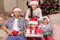 摆在与礼物的俏丽的家庭在圣诞节期间 免版税库存照片
