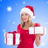 摆在与礼物盒的圣诞老人帽子的可爱的愉快的妇女 免版税库存照片