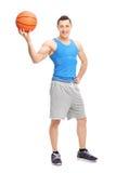 摆在与篮球的英俊的年轻人在他的手上 免版税库存照片