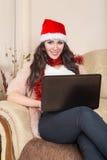 摆在与红色圣诞老人帽子的微笑的少妇画象  库存照片