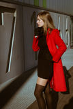 摆在与红色外套的美丽的女孩 免版税库存图片