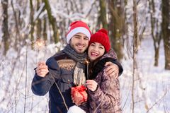 摆在与红色帽子, bengals的愉快的夫妇在冬天停放 免版税库存图片