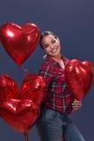 摆在与红色心形的气球的美丽的妇女 免版税库存图片