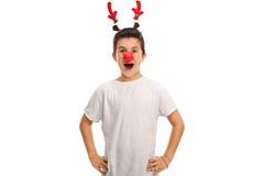 摆在与红色鹿角和一个红色鼻子的男孩 免版税库存照片