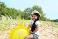 摆在与纸太阳的嬉戏的女孩 免版税库存图片