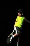 摆在与网球设备清洁运动鞋的英俊的男孩 免版税库存图片