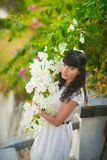 摆在与美丽的白花的白色礼服的女孩 免版税库存图片