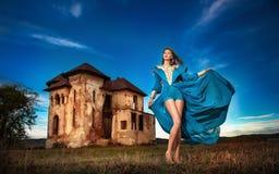 摆在与老城堡和多云剧烈的天空的长的蓝色礼服的时兴的美丽的少妇在背景中 免版税库存照片