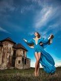 摆在与老城堡和多云剧烈的天空的长的蓝色礼服的时兴的美丽的少妇在背景中 库存照片