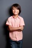 摆在与胳膊的凉快的小男孩横渡 免版税库存图片