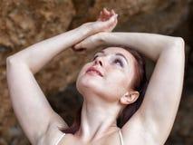 摆在与胳膊的女性在岩石附近上升了 图库摄影