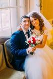 摆在与葡萄酒内部的窗口背景附近的Enloved夫妇 婚礼礼服的新娘坐膝盖她 库存照片