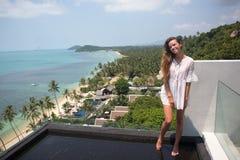 摆在与蓝色海洋的惊人的热带海滩的年轻人相当时髦的肉欲的妇女享受她的假日和一有风summe 免版税图库摄影