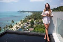 摆在与蓝色海洋的惊人的热带海滩的年轻人相当时髦的肉欲的妇女享受她的假日和一有风summe 免版税库存照片