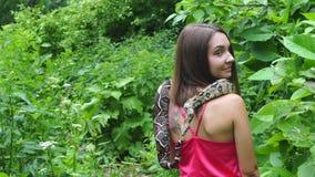 摆在与蛇的女孩在他的在自然的脖子上 股票视频