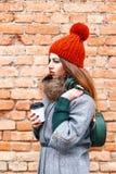 摆在与袋子的年轻时装模特儿女孩咖啡和温暖的wi 库存图片
