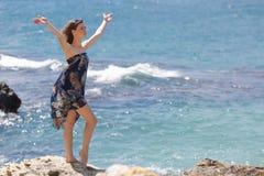 摆在与被举的胳膊的岩石的sundress的赤足女孩 图库摄影
