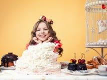 摆在与许多的愉快的微笑的女孩甜点 库存照片