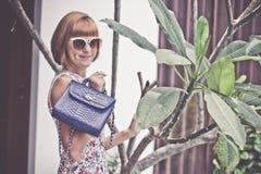 年轻摆在与豪华手工制造snakeskin Python提包的魅力妇女佩带的花礼服 时髦美丽的女孩 库存照片