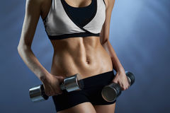 摆在与重量的体育齿轮的女性 免版税图库摄影