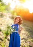 摆在与野花花束的一件蓝色礼服的一个年轻深色的女孩在明亮的太阳的光芒的一个公园 库存图片