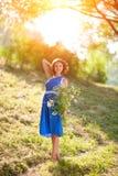 摆在与野花花束的一件蓝色礼服的一个年轻深色的女孩在明亮的太阳的光芒的一个公园 图库摄影