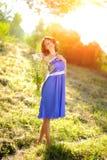 摆在与野花花束的一件蓝色礼服的一个年轻深色的女孩在明亮的太阳的光芒的一个公园 库存照片