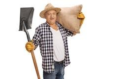 摆在与铁锹和粗麻布大袋的年长农夫 免版税图库摄影