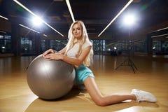 摆在与银色瑜伽球的体育衣物的白肤金发的妇女 免版税库存图片