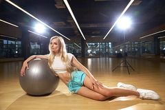 摆在与银色瑜伽球的体育衣物的白肤金发的妇女 免版税库存照片