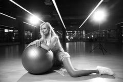 摆在与银色瑜伽球的体育衣物的白肤金发的妇女 库存图片