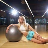 摆在与银色瑜伽球的体育衣物的白肤金发的妇女 库存照片