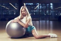 摆在与银色瑜伽球的体育衣物的白肤金发的妇女 图库摄影