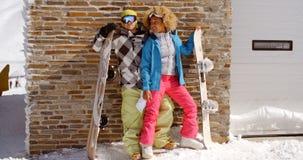 摆在与雪板的接近的夫妇反对车库 免版税库存图片