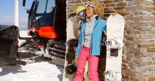 摆在与雪板的接近的夫妇反对车库 库存图片