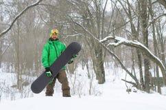 摆在与雪板的明亮的衣裳的挡雪板 免版税库存图片