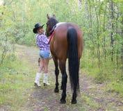 摆在与马的白肤金发的女牛仔妇女 免版税库存图片