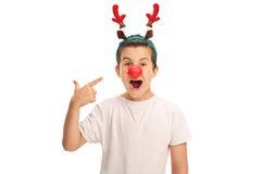 摆在与驯鹿耳朵和鼻子的男孩 图库摄影